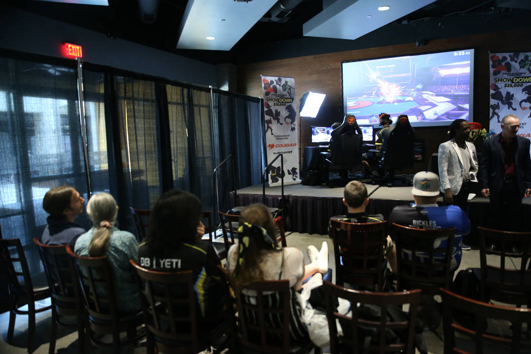 Players compete in the Super Smash Bros. Ultimate Showdown tournament at GameWorks in Las Vegas ...