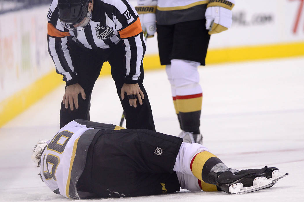 Vegas Golden Knights center Erik Haula (56) lies on the ice after taking a hit along the boards ...