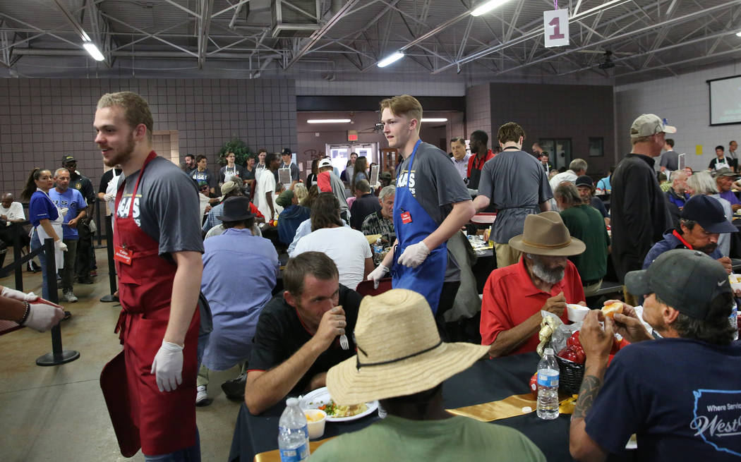 Vegas Golden Knights Development Camp participants prepare to serve a meal to clients as they p ...
