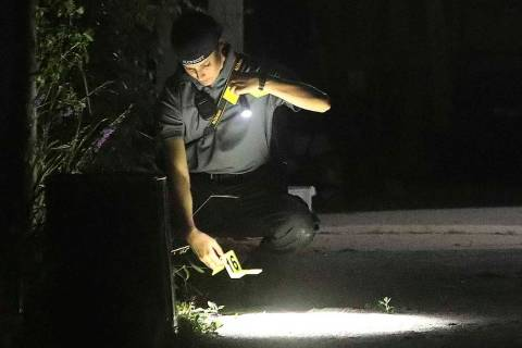 Technicians process the driveway of a home as Salt Lake City Police serve a search warrant at t ...