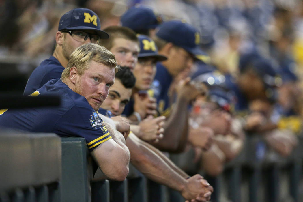 Michigan players including Miles Lewis, left, follow the ninth inning of Game 3 of the NCAA Col ...
