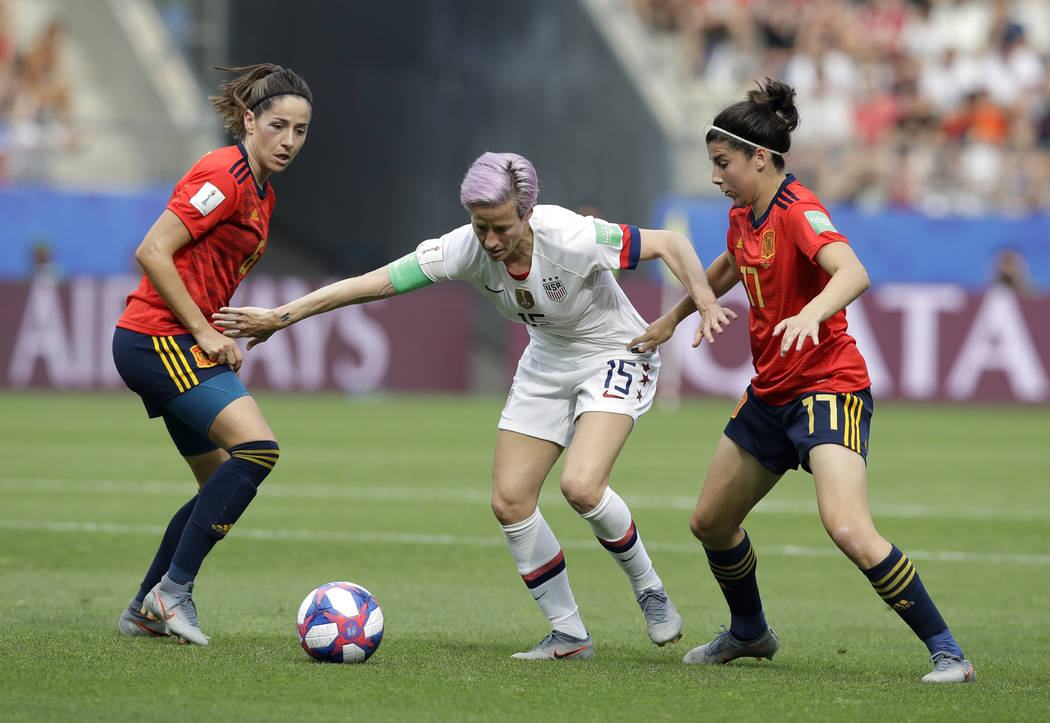United States'Megan Rapinoe, middle, is challenged by Spain's Vicky Losada, left, and her teamm ...