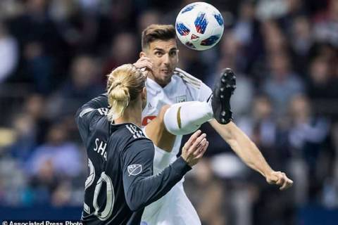 Los Angeles FC's Dejan Jakovic, back, leaps to kick the ball away from Vancouver Whitecaps' Bre ...