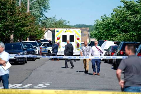 FILE -- New York City Police officials gather along Wilcox Street behind the 121st Precinct sta ...