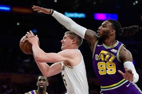 Los Angeles Lakers center Moritz Wagner, left, tries to shoot as Utah Jazz forward Jae Crowder ...