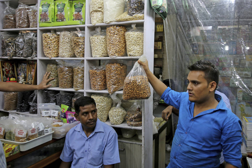 In this Saturday, June 22, 2019 photo, a salesman holds a bag of California almond kernels for ...