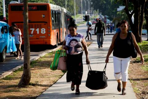 Women carry a bag after arriving by bus to Havana, Cuba, Thursday, June 27, 2019. Cuban Preside ...