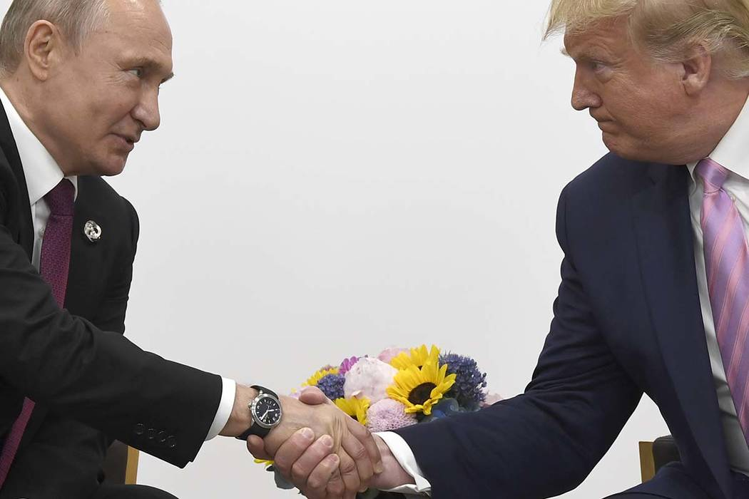 President Donald Trump, right, shakes hands with Russian President Vladimir Putin during a bila ...