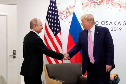 U.S. President Donald Trump, right, shakes hands with Russian President Vladimir Putin during a ...