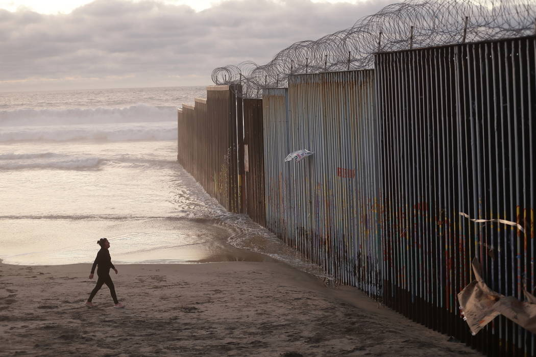 FILE - In this Jan. 9, 2019 file photo, a woman walks on the beach next to the border wall topp ...