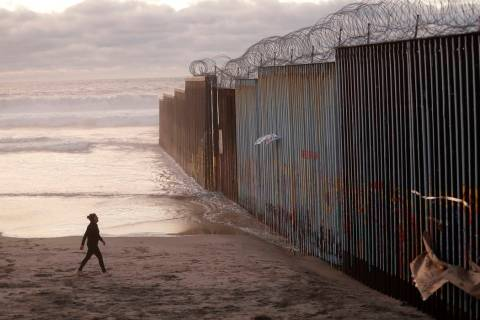 A woman walks on the beach next to the border wall topped with razor wire in Tijuana, Mexico, i ...