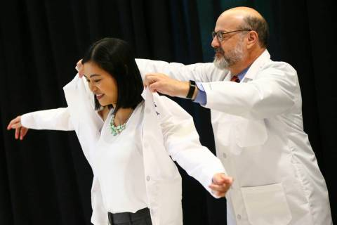 Tom Hunt, family medicine program director at Valley Health System, right, puts a coat onto fam ...