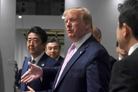 President Donald Trump, walking with Japanese Prime Minister Shinzo Abe stops to ask a question ...