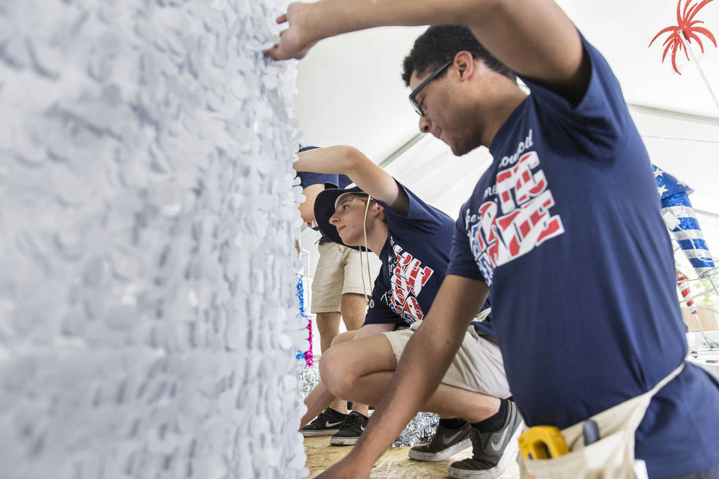Connor Jordan, center, and Dwight Jones work on a float during preparation for the Summerlin Pa ...
