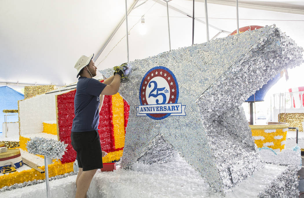 Julien Mihy works on a float during preparation for the Summerlin Patriotic Parade on Saturday, ...