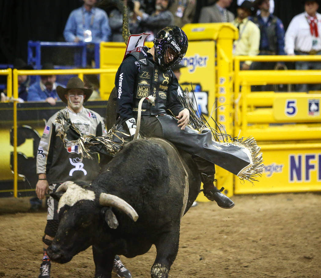 "Sage Kimzey of Strong City, Okla. (3) rides ""Joker"" while competing Bull Riding durin ..."