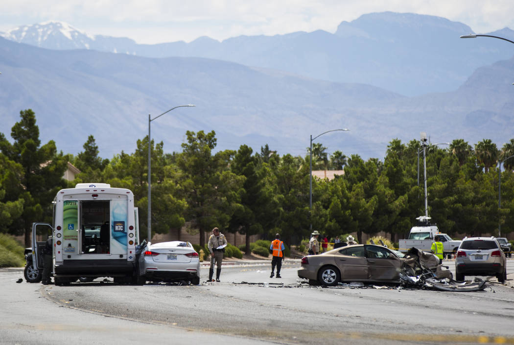 Las Vegas police investigate the scene of an accident involving three cars and a bus on Lake Me ...