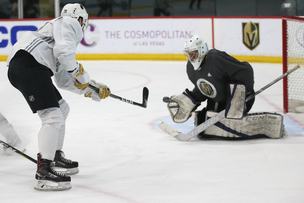 Vegas Golden Knights' Justin Ducharme, left, takes a shot at goaltender Isaiah Saville during a ...