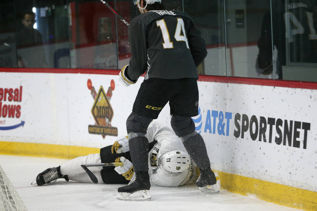 Vegas Golden Knights' Nicolas Hague (14) stands over Jack Dugan (51) after he took a fall durin ...
