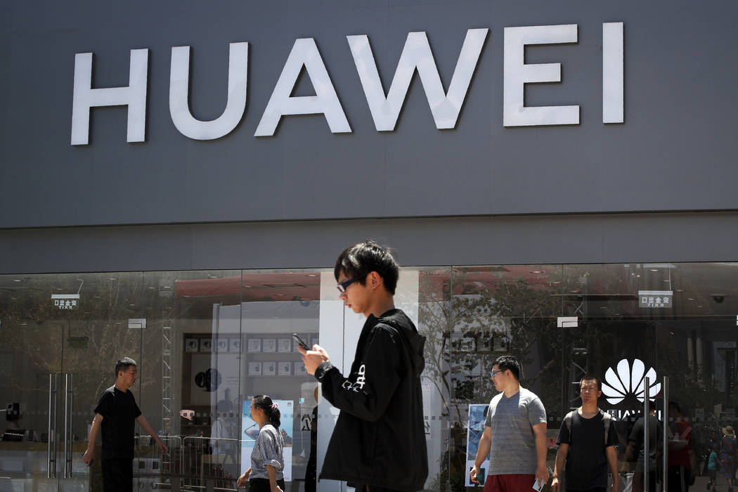 People walk past a Huawei retail store in Beijing, Sunday, June 30, 2019. Once again, President ...