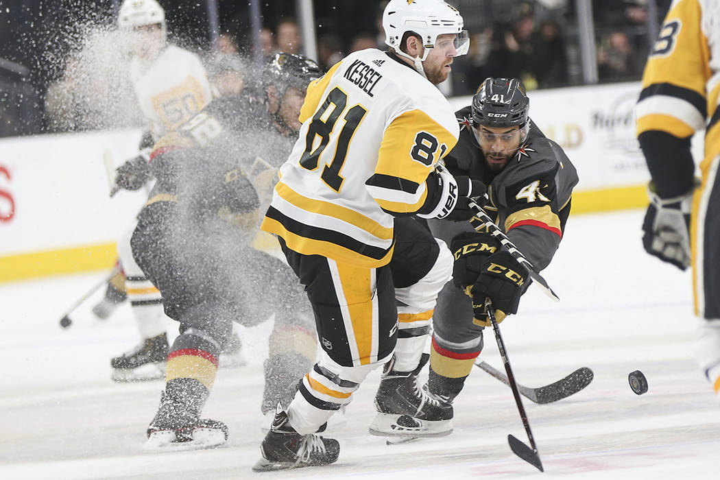 Golden Knights center Pierre-Edouard Bellemare (41) sends the puck past Pittsburgh Penguins rig ...