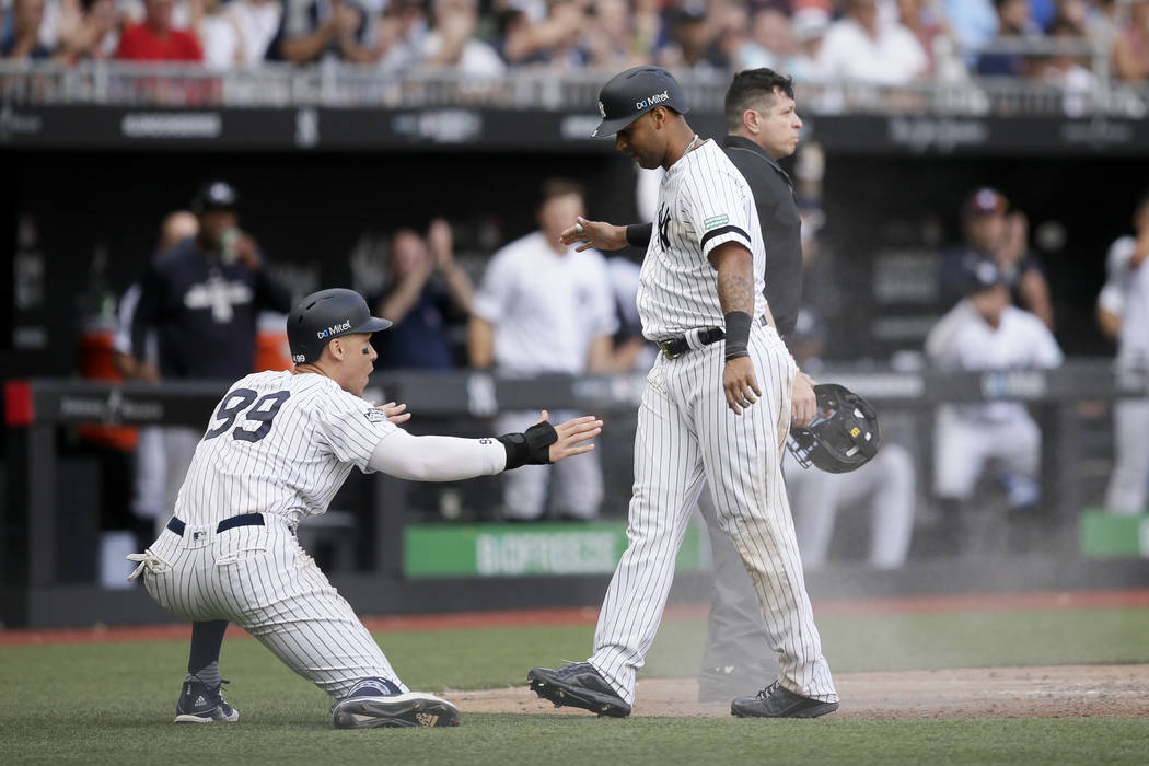 New York Yankees' Aaron Judge, left, and Aaron Hicks celebrate after scoring on a single by Gar ...
