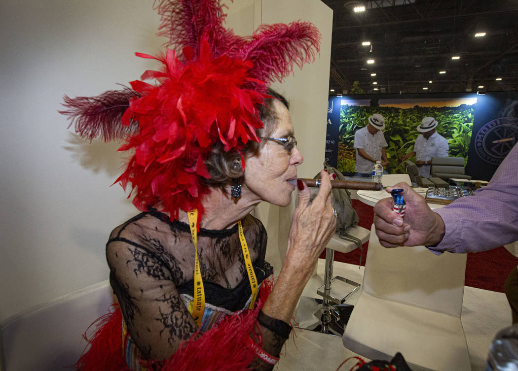 Suzanne Wilson, owner of Smoke Signals in Tombstone, Ariz., puffs a cigar from the help of Jack ...