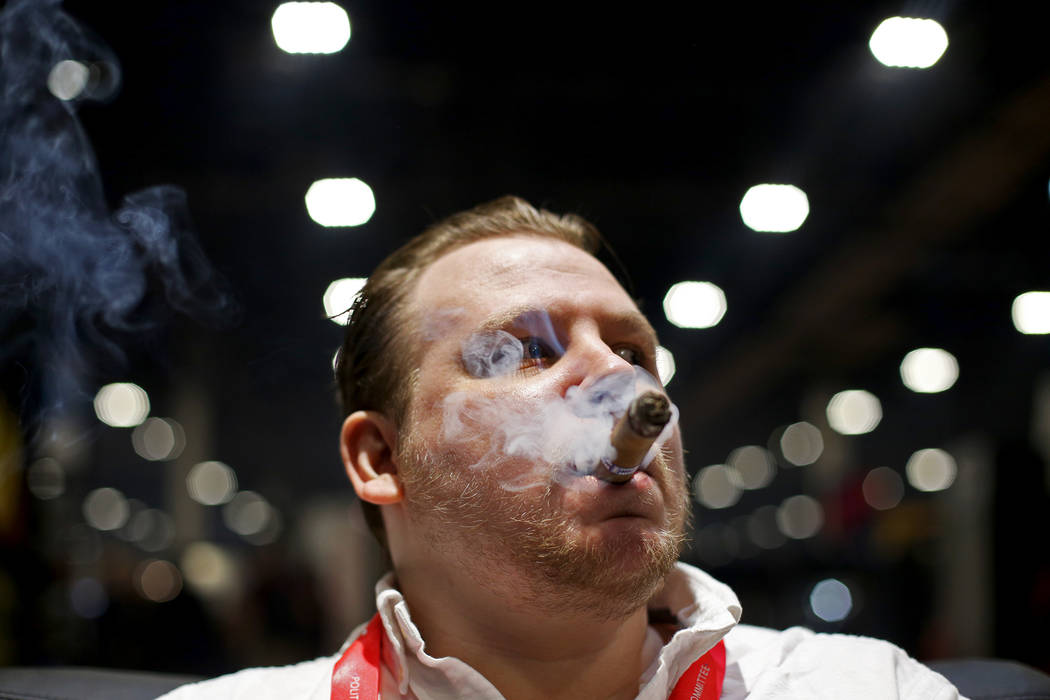 Ethan Bradon smokes a cigar at the Serino Cigar Company booth at the International Premium Ciga ...