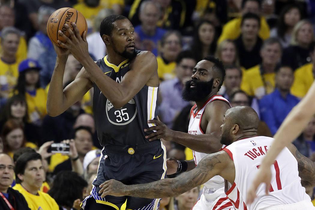 Golden State Warriors' Kevin Durant, left, is defended by Houston Rockets' James Harden, center ...