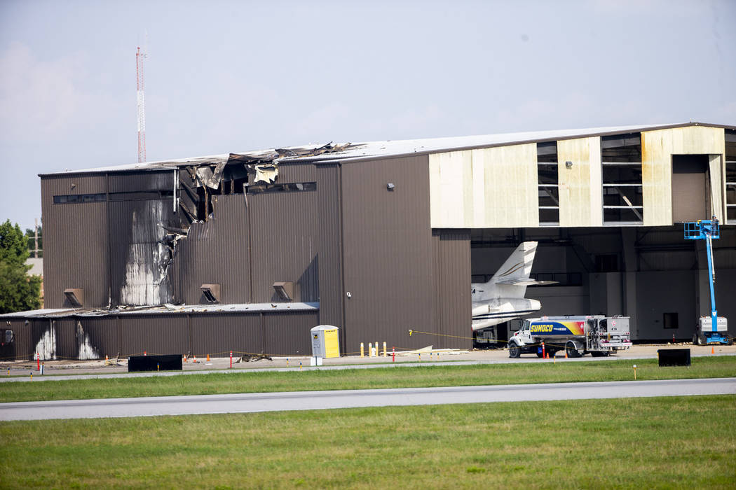 Damage is seen to a hangar after a twin-engine plane crashed into the building at Addison Airpo ...
