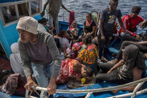 Migrants rest after being rescued at sea by the Open Arms aid boat on Sunday June 30, 2019. A h ...
