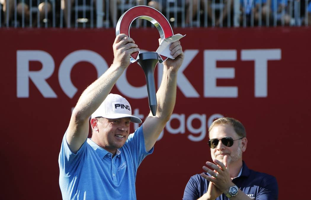 Nate Lashley raises the winner's trophy after the final round of the Rocket Mortgage Classic go ...