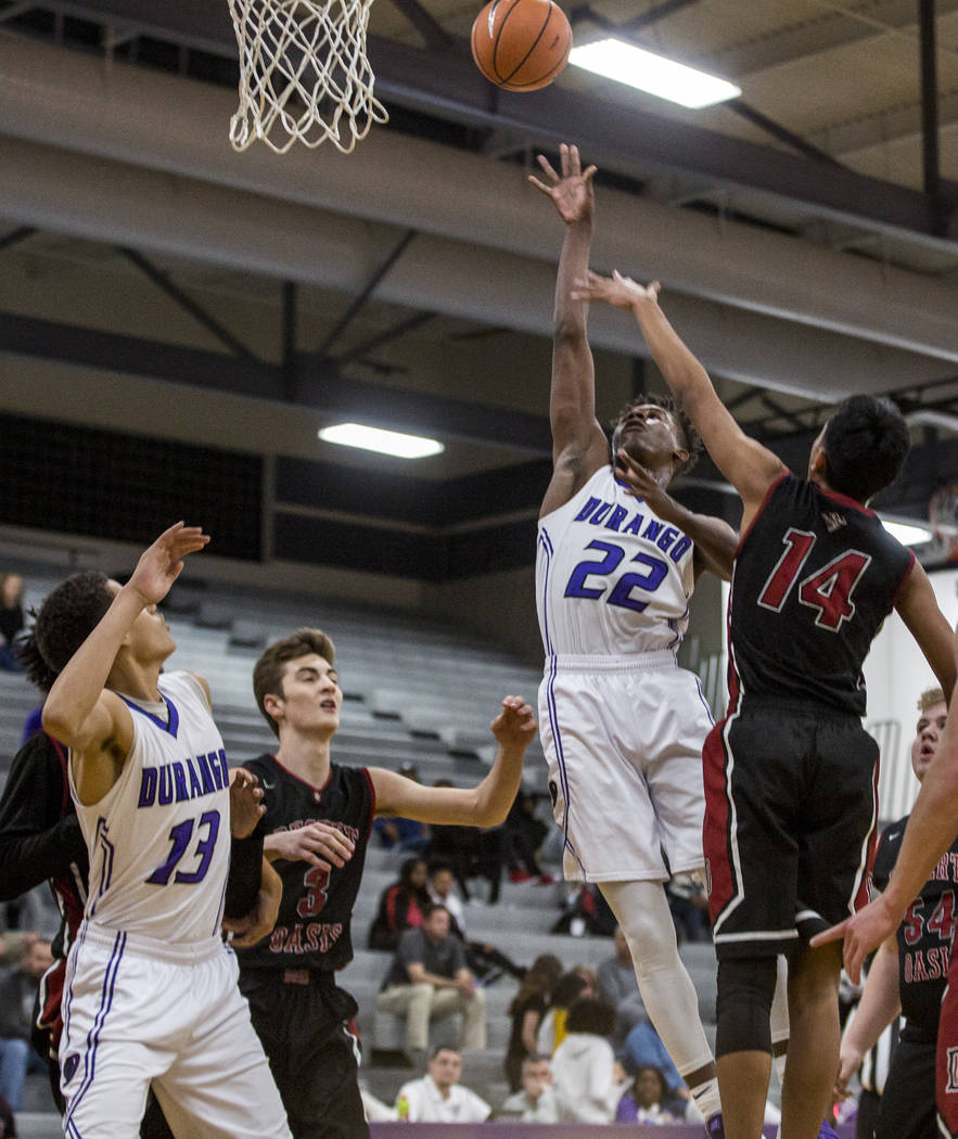 Durango's Vernell Watts (22) attempts a layup while Anthony Swift (13) watches and Des ...