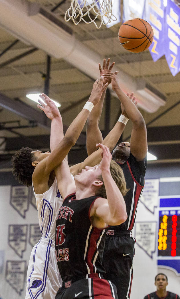 Durango's Vernell Watts (22) left, reaches for the ball as Desert Oasis players Jacob ...
