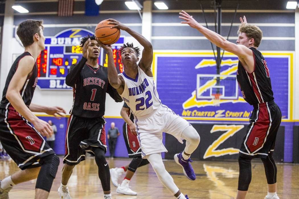 Durango's Vernell Watts (22) looks for a shot against the defense of Desert Oasis&#821 ...