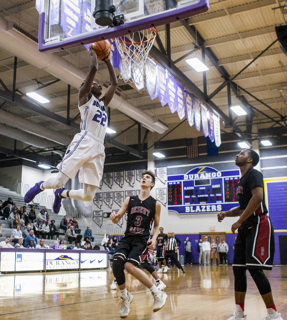 Durango's Vernell Watts (22) dunks while Desert Oasis' Cade Savell (3) and Manny ...