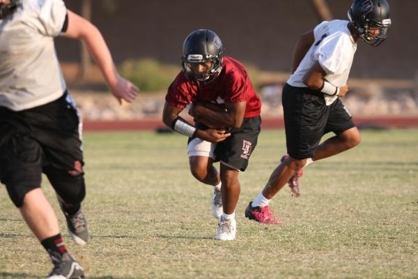 Running back Tyshun McClinton, center, participates in football practice at Desert Oasis Hig ...
