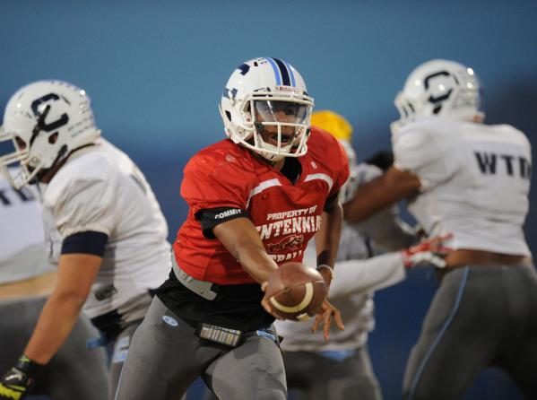 Centennial quarterback Jamaal Evans hands off the ball during their football practice at Cen ...