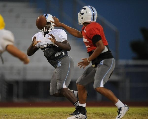 Centennial quarterback Jamaal Evans flips the ball to running back Rhamondre Stevenson durin ...