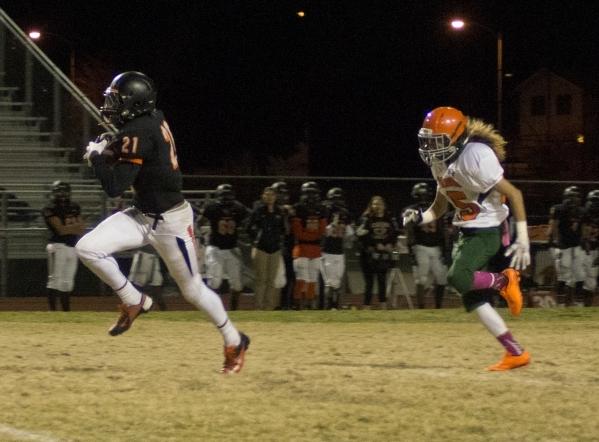 Chaparral's Casey Acosta (21) runs the ball against Mojave High School's defense ...