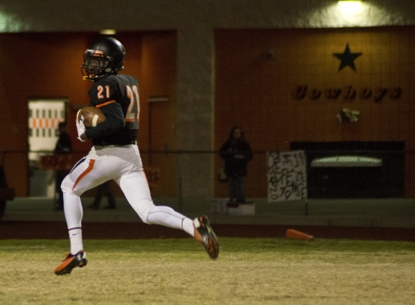 Chaparral's Casey Acosta (21) looks behind him as he runs toward the end zone in the f ...