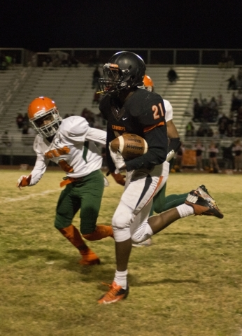 Chaparral's Casey Acosta (21) runs the ball while pursued by Mojave's Kevin John ...