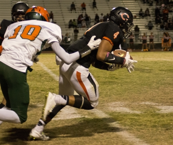 Chaparral's Richard Hernandez (4) intercepts a pass and is tackled by Mojave's A ...