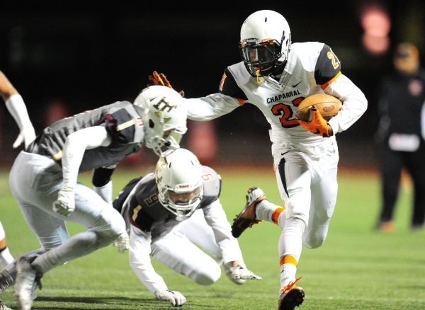 Chaparral wide receiver Casey Acosta (21) attempts to stiff-arm Faith Lutheran defensive bac ...