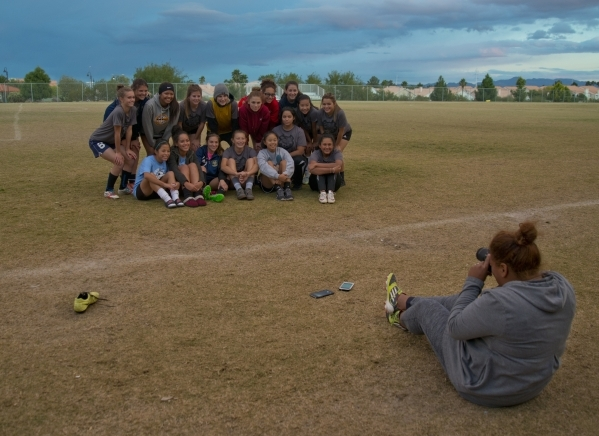 Spring Valley High School girls soccer coach Yamilza Rivera takes a photo of her players aft ...