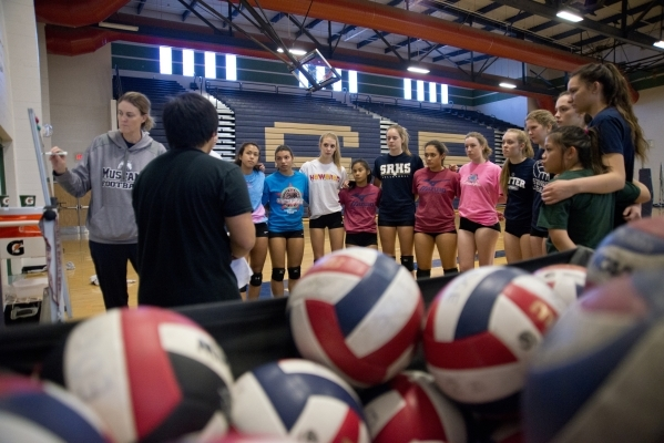 Players on the Shadow Ridge girls volleyball team receive instructions from coaches during p ...