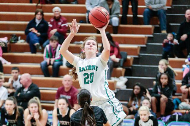 Green Valley junior Brooke Haney (20) leaps above Desert Oasis freshman Brianna Clark (4) wh ...