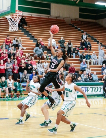 Desert Oasis freshman Ahmaya Smith (15) leaps up to make a basket while surrounded by Green ...