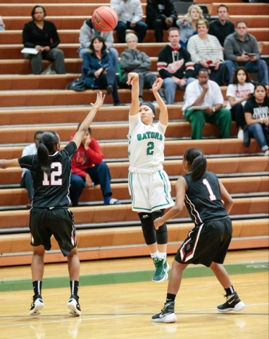 Green Valley senior Gwen Garcia (2) attempts a shot from the three point line, while Desert ...
