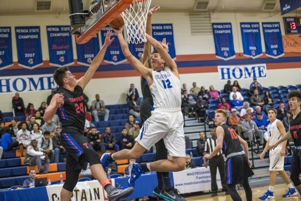 Bishop Gorman center Zach Collins (12) takes the ball to the basket while being defended by ...